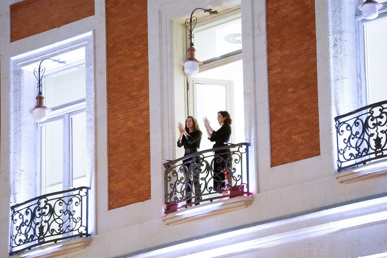 Díaz Ayuso (derecha) se sumó al homenaje a los sanitarios aplaudiendo desde el balcón de la Real Casa de Correos