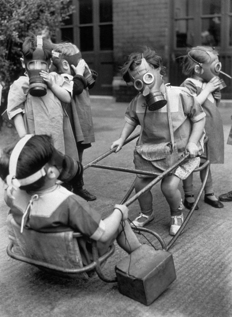 Niños y niñas jugando en la calle con máscaras de gas (1940)